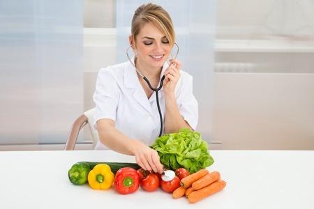 野菜に聴診器を当てて栄養成分をチェックする女性